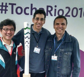 Eu e meus amigos e sócios, em frente à tocha olímpica na sede do COI, no Rio de Janeiro
