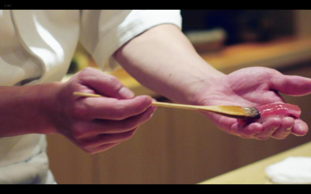 Cena de Jiro Dreams of Sushi: chef passando (pouco) shoyu no sushi com pincel