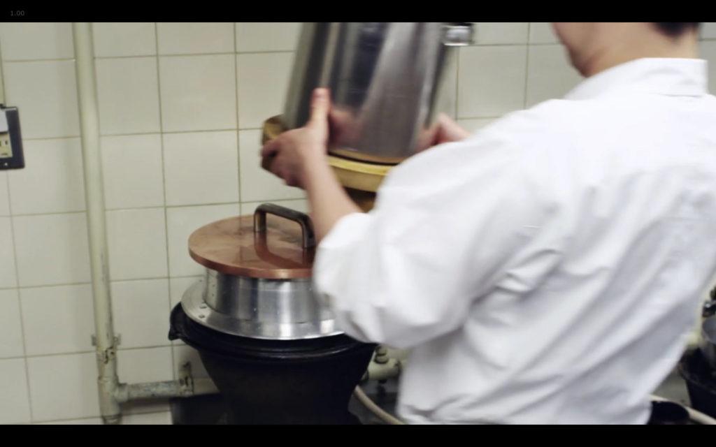Cena de Jiro Dreams of Sushi: cozimento do arroz para sushi na pressão. Note que o peso extra é formado por uma panela com água. Tudo bem tradicional.