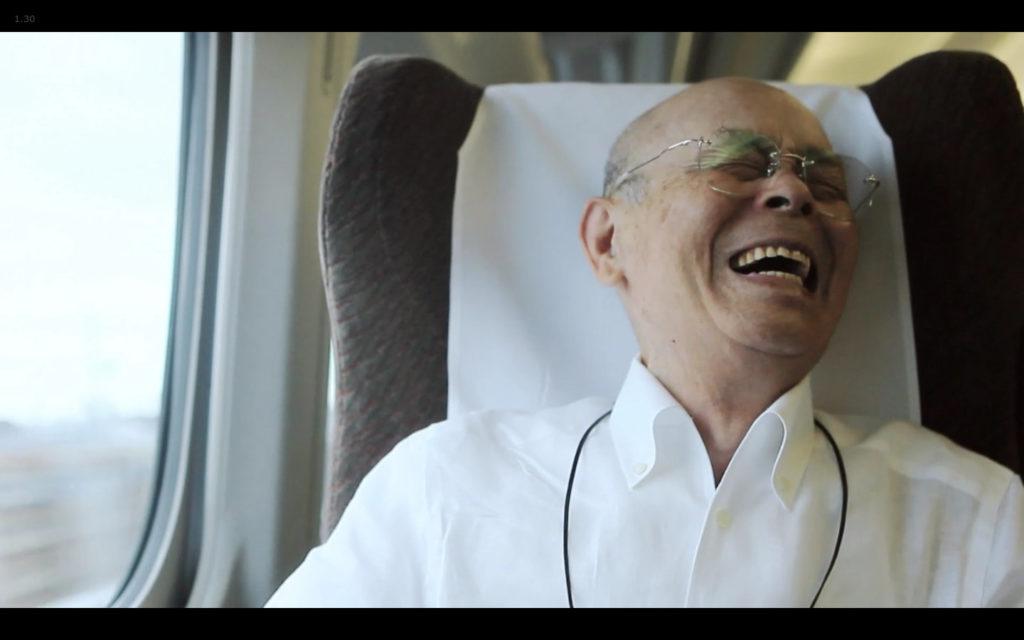 Cena de Jiro Dreams of Sushi: Jiro Ono sorrindo ao contar que não era um bom exemplo quando foi dar uma palestra para alunos de uma escola